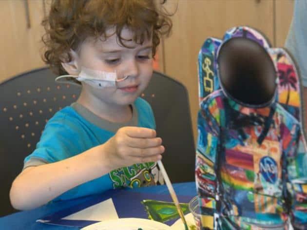 Niño con cancer pintando traje de astronauta